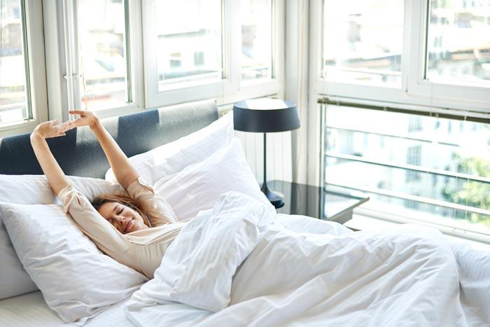 потягивается в кровати