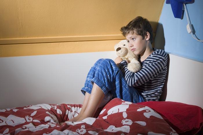 грустный мальчик на кровати