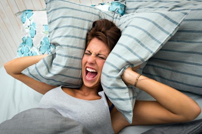 закрывает уши подушками