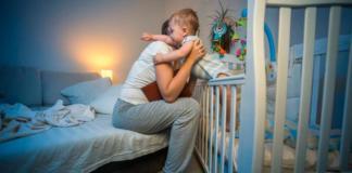 достает ребенка из кровати