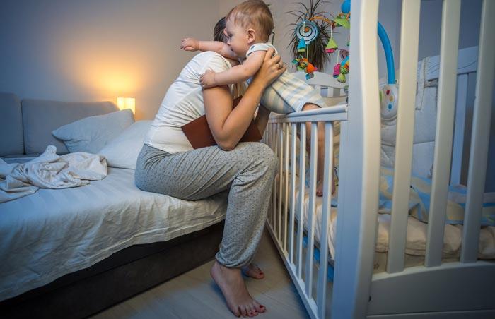 достает малыша из кроватки